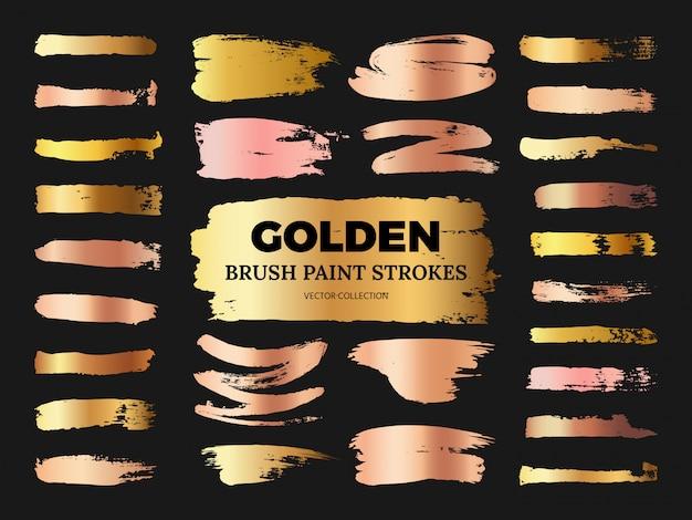 Collection de traits de peinture au pinceau grunge rose et doré dessinés à la main isolée sur fond noir