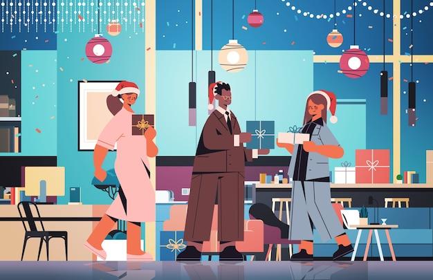 Collègues en chapeaux de père noël tenant des cadeaux mélanger des collègues de course célébrant le nouvel an et les vacances de noël bureau intérieur illustration vectorielle pleine longueur horizontale