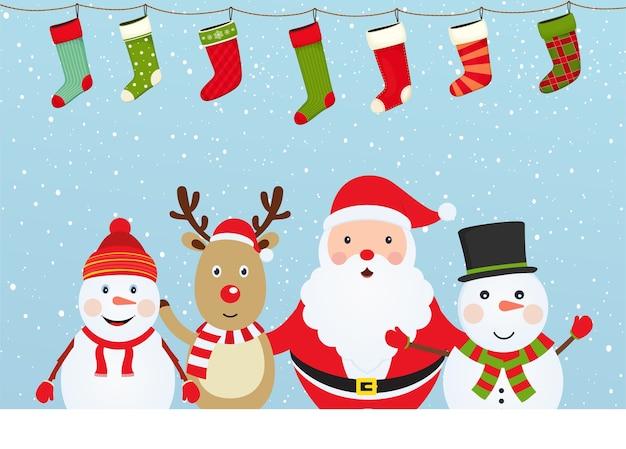 Composition de noël avec le père noël, le bonhomme de neige et le cerf sur fond neigeux avec des chaussettes de noël.