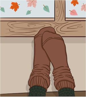 Composition de pieds en chaussettes brunes maintenues contre une fenêtre tandis que les feuilles tombent à l'extérieur.