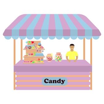 Comptoir de décrochage avec des sucettes de bonbons le vendeur masculin se tient derrière le comptoir