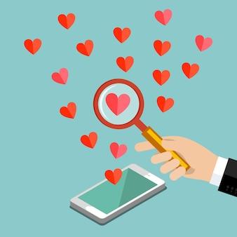 Concept d'amour ou de relation. la main avec une loupe regarde le cœur.