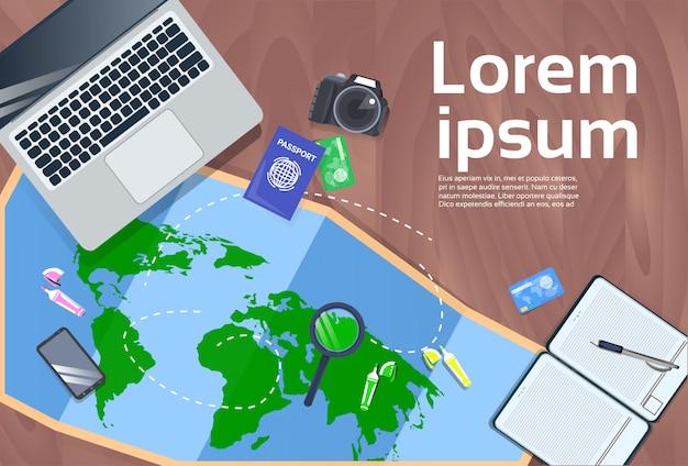 Concept de bureau de planification de vacances et de voyage avec ordinateur portable, carte, appareil photo et vue de dessus de passeport