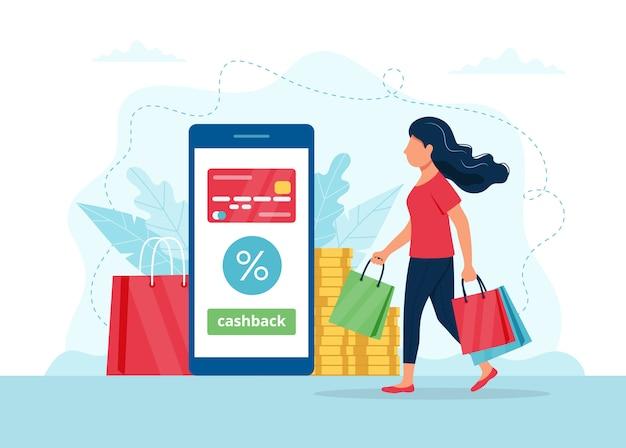 Concept de cashback - femme avec des sacs à provisions, smartphone avec carte de crédit dessus.