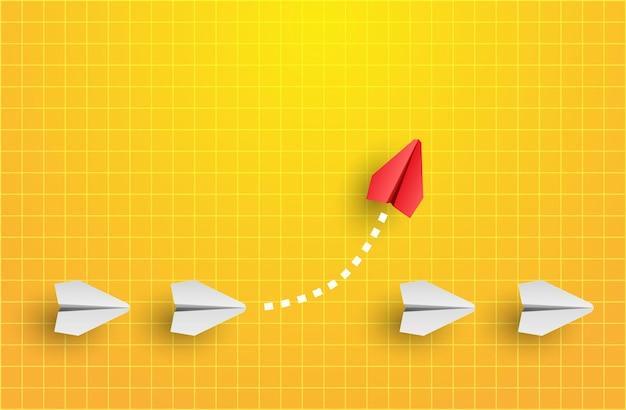 Concept d'individualité un avion en papier rouge leader individuel et unique vole sur le côté. penser différemment