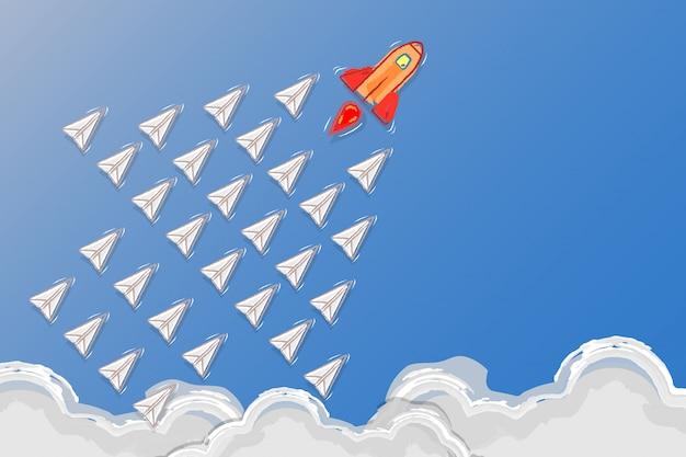 Concept de leadership, de travail d'équipe et de courage, rocket pour le leader et avions en papier volant suivent le leader de la fusée dans le ciel.