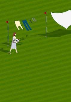 Concept d'utilisation différente: femme au foyer, vêtements suspendus à sécher sur une corde à linge sur un parcours de golf.