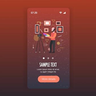 Concepteur d'homme tenant des échantillons de palette de couleur enregistrement d'un blogueur vidéo en ligne avec un appareil photo numérique sur un trépied concept de blogage de réseau social smartphone application mobile pleine longueur