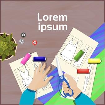 Concepteur de mode table de travail vue de dessus en angle de travail concept concept mains tenant des ciseaux tissu, tissu