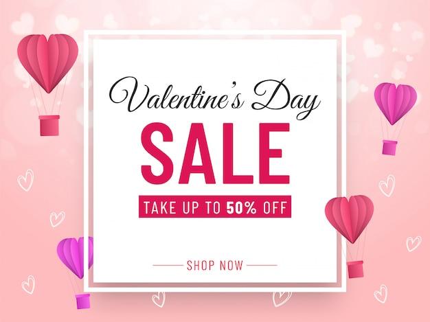 Conception de bannière de vente de la saint-valentin avec offre de réduction de 50%, ballons à air chaud en papier découpé et coeurs décorés sur fond rose.