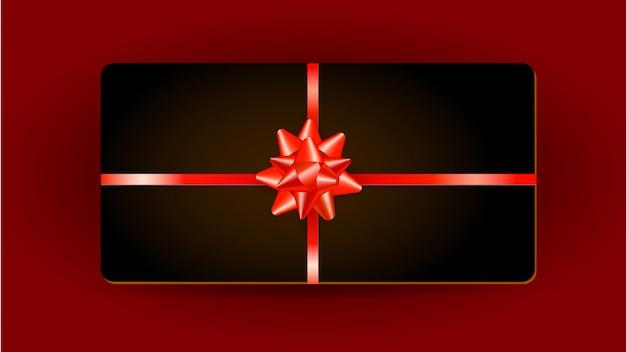 Conception de carte cadeau avec ruban rouge et noeud cadeau isolé sur rouge