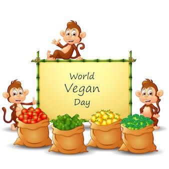 Conception de texte de la journée mondiale végétalienne sur signe avec des légumes et des singes