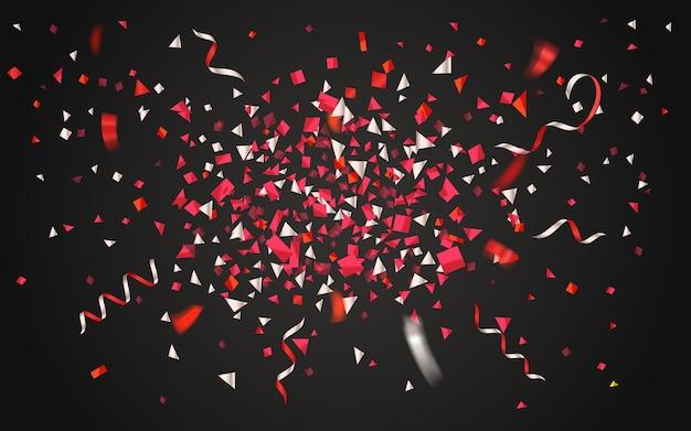 Confettis colorés et rubans sur fond sombre