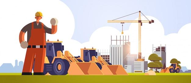 Constructeur masculin dans un casque, agitant un ouvrier à la main, debout près d'un tracteur lourd, excavateur, travailleur industriel, en uniforme, concept de construction, site de construction, fond, plat, pleine longueur, horizontal