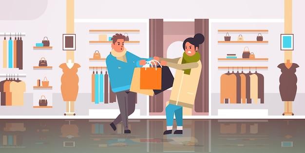 Couple d'acheteurs se battant pour le dernier coffret cadeau homme femme clients tirant des achats dans différentes directions vente lutte contre les achats saisonniers