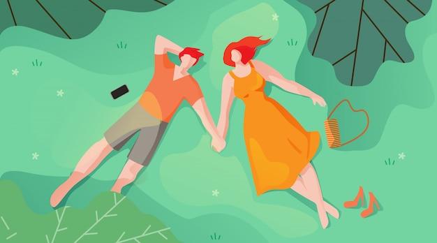 Couple amoureux mentez sur l'herbe et regardez le ciel plat.