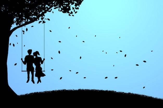 Couple d'amoureux s'installant ensemble sur une balançoire sous le grand arbre.
