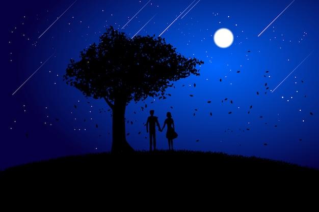 Couple d'amoureux de silhouette tenant la main sous le fond de grand arbre dans la nuit.