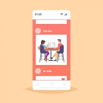 Couple d'architectes à l'aide d'ingénieurs portables projet de maison de rédaction sur écran d'ordinateur avec des plans de logement des entrepreneurs ing plan de maison application mobile en ligne pleine longueur