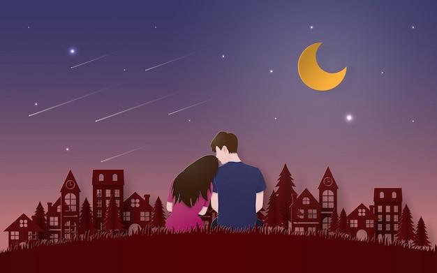 Couple assis sur le sol en herbe à la recherche de météore