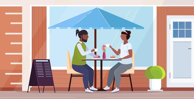 Couple assis à table manger un gâteau sucré en surpoids homme femme passer du temps ensemble nutrition malsaine obésité concept rue moderne café extérieur pleine longueur horizontale