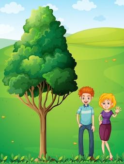 Un couple au sommet de la colline se tenant près de l'arbre