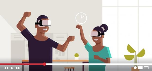 Couple de blogueurs portant des lunettes vr casque afro-américain homme femme explorant la réalité virtuelle lunettes numériques enregistrement vidéo streaming en direct blogging concept portrait horizontal