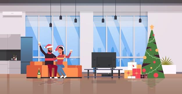 Couple, boire, champagne, joyeux noël, bonne année, vacances, célébration, veille, fête, concept, homme femme, dans, santa, chapeaux, séance table, salon moderne, intérieur, pleine longueur, horizontal, vecteur, illust