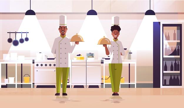 Couple de chefs professionnels tenant des plateaux couverts servant des plateaux femme afro-américaine homme en uniforme debout ensemble cuisson concept alimentaire cuisine moderne intérieur
