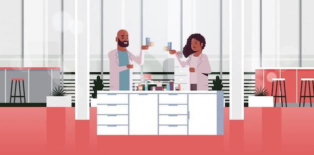 Couple de chercheurs détenant des paquets de médicaments