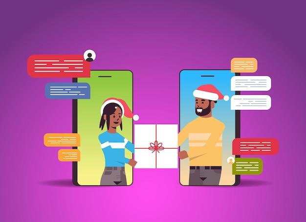 Couple, dans, chapeaux santa, utilisation, bavarder, application, réseau social, chat, bulle, communication, concept