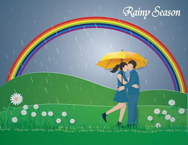 Couple debout sur l'herbe verte et l'arc-en-ciel