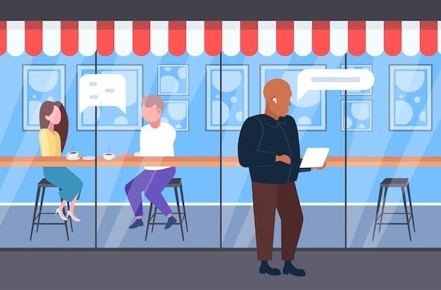 Couple, discuter, pendant, réunion, homme, utilisation, mobile, app, bulle, bavarder, médias sociaux, communication, concept, visiteurs, discours, conversation, amusant, moderne, rue, café, pleine longueur, horizontal