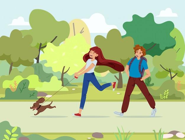 Couple d'écoliers heureux marcher dans le parc avec un chien