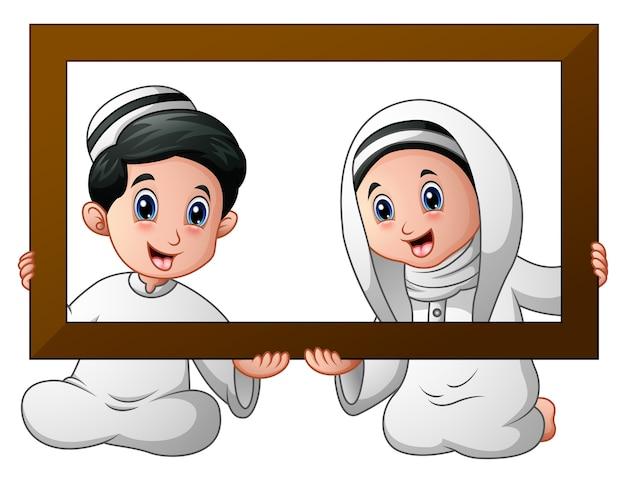 Couple d'enfant musulman tenant cadre en bois et de célébrer le ramadan