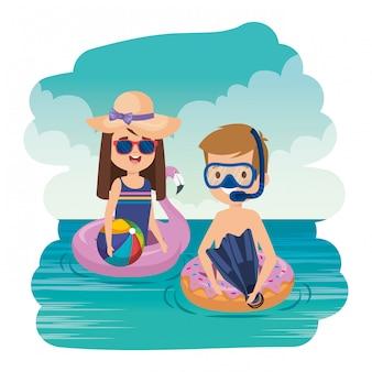 Couple d'enfants avec tuba et ballon sur la mer
