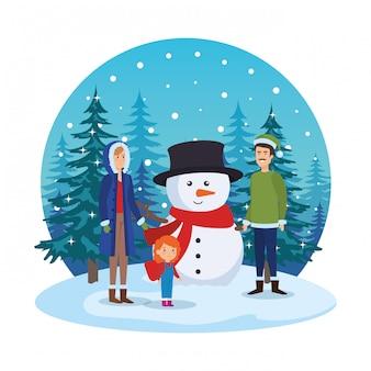 Couple avec fille et bonhomme de neige dans le paysage de neige