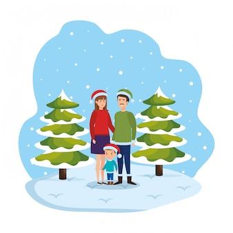 Couple et fils avec des vêtements d'hiver dans le paysage de neige