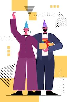 Couple gay dans des chapeaux de fête célébrant la parade d'amour transgenre concept de communauté lgbt illustration vectorielle verticale pleine longueur