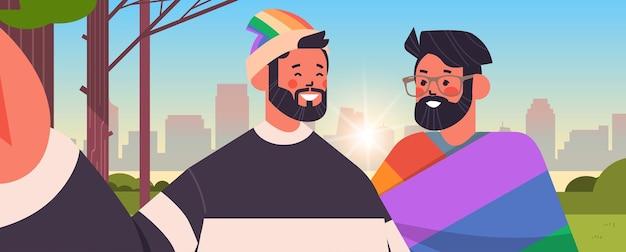 Couple gay avec drapeau arc-en-ciel prenant une photo de selfie sur l'appareil photo d'un smartphone transgenre aime la communauté lgbt