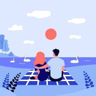 Couple heureux assis près du lac au coucher du soleil