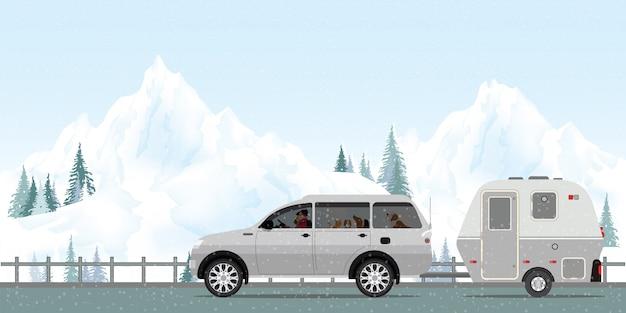 Couple heureux au volant d'une voiture sur la route en hiver