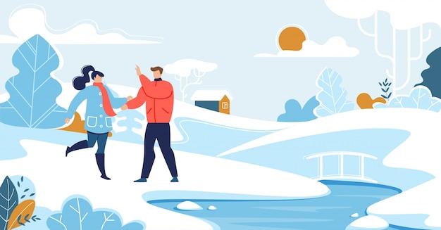 Couple homme et femme à pied dans le parc enneigé près de la rivière