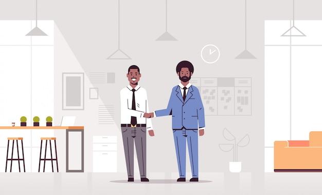 Couple hommes, poignée main, partenaires affaires, poignée main, pendant, réunion, accord, partenariat, concept, coworking, centre, moderne, bureau, intérieur, pleine longueur, horizontal