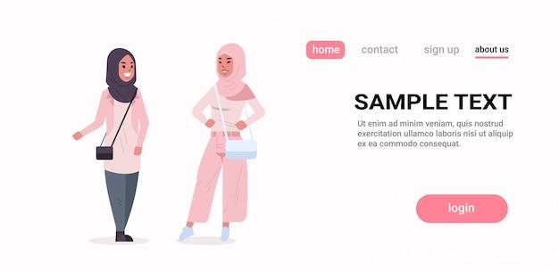 Couple ic femmes en hijab discutant des filles arabes portant des vêtements traditionnels foulard debout ensemble concept de communication pleine longueur copie horizontale espace plat