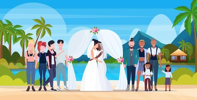 Couple, nouveaux mariés, lesbiennes, dans, robe blanche, debout, derrière, arc, même sexe, marié, famille homosexuelle, mariage, célébrer, concept, île tropicale, paysage marin, paysage, fond, pleine longueur, horizontal