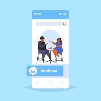 Couple obèse manger un gâteau savoureux sucré femme en surpoids nourrir son gros copain afro-américain nutrition malsaine obésité concept écran smartphone application mobile en ligne