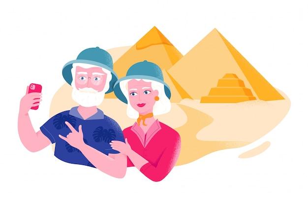 Couple de personnes âgées en chapeaux de safari prend selfie près des pyramides égyptiennes.