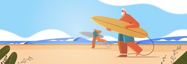 Couple de personnes âgées avec des planches de surf homme femme surfeurs tenant des planches de surf vacances d'été concept de vieillesse active