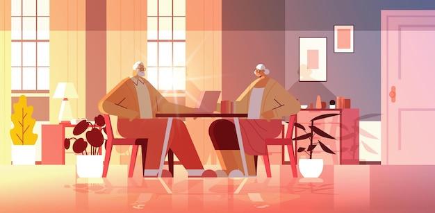 Couple de personnes âgées utilisant un ordinateur portable, grands-parents se relaxant à la maison, concept de communication en ligne du réseau de médias sociaux
